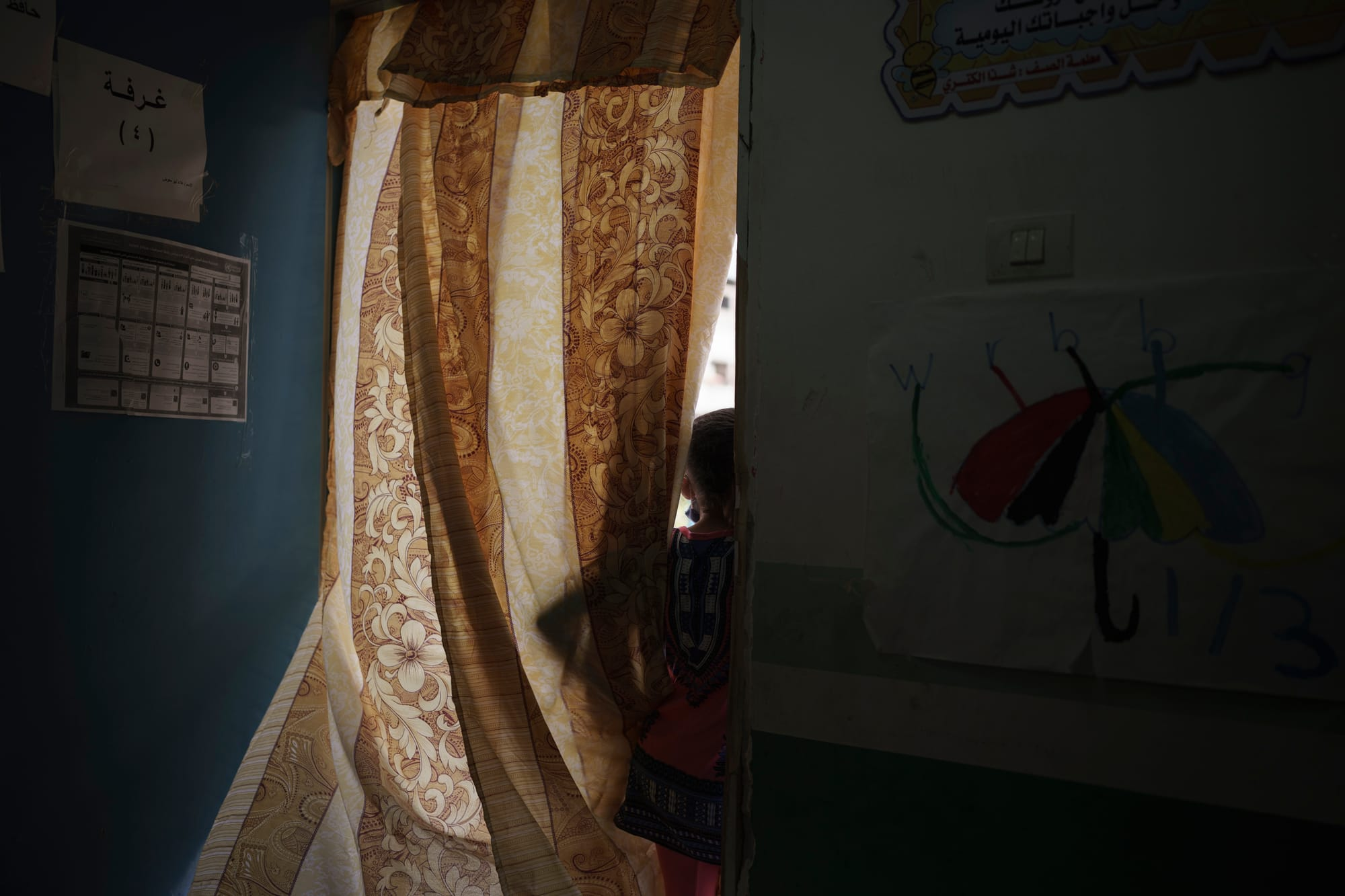 A 10-year-old girl looks outside from the window of a classroom in a school run by the U.N. where her family took shelter after their home was destroyed during the recent 11-day war, in Jabaliya refugee camp.