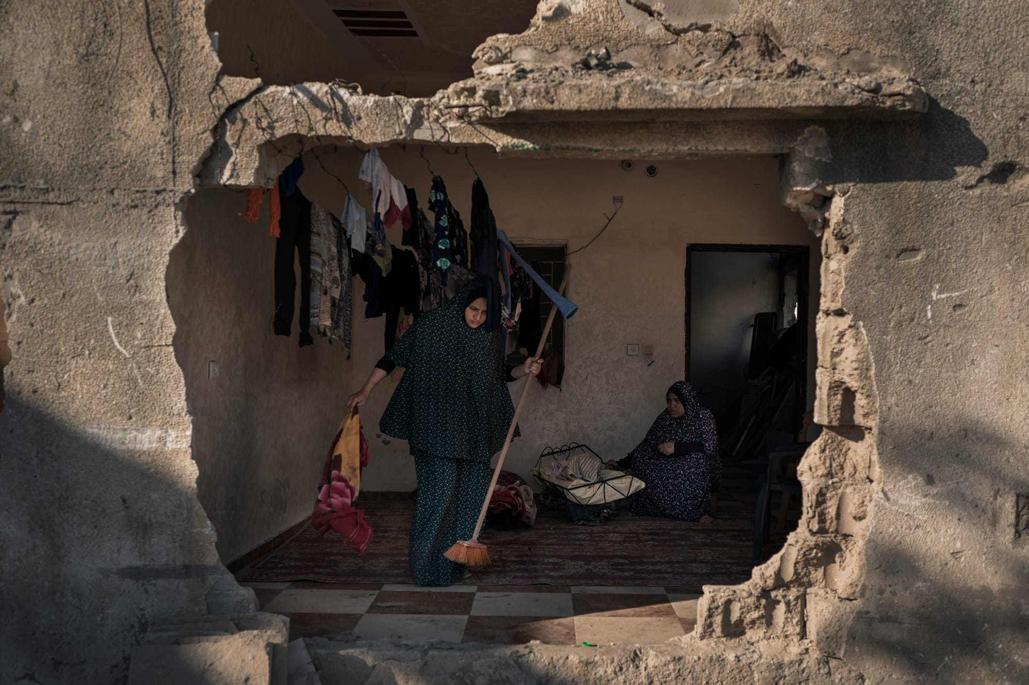 A woman cleans a room inside her home that was heavily damaged by airstrikes in Gaza. She is one of the residents trying to bring stability amid destruction. But their fears linger, knowing that sooner or later, war could erupt again.