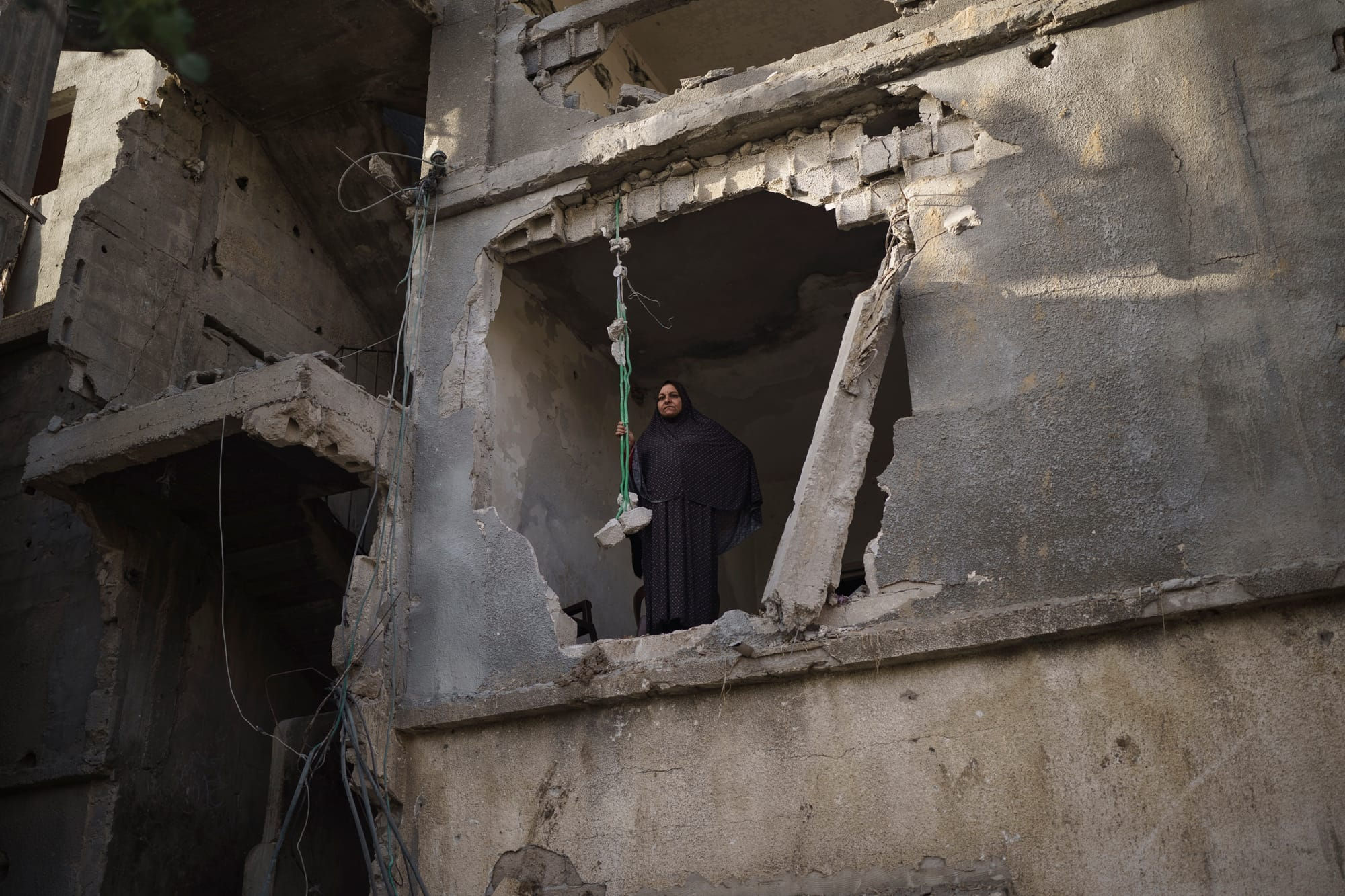 Jawaher Nassir looks down on the street from a room in her heavily-damaged home.