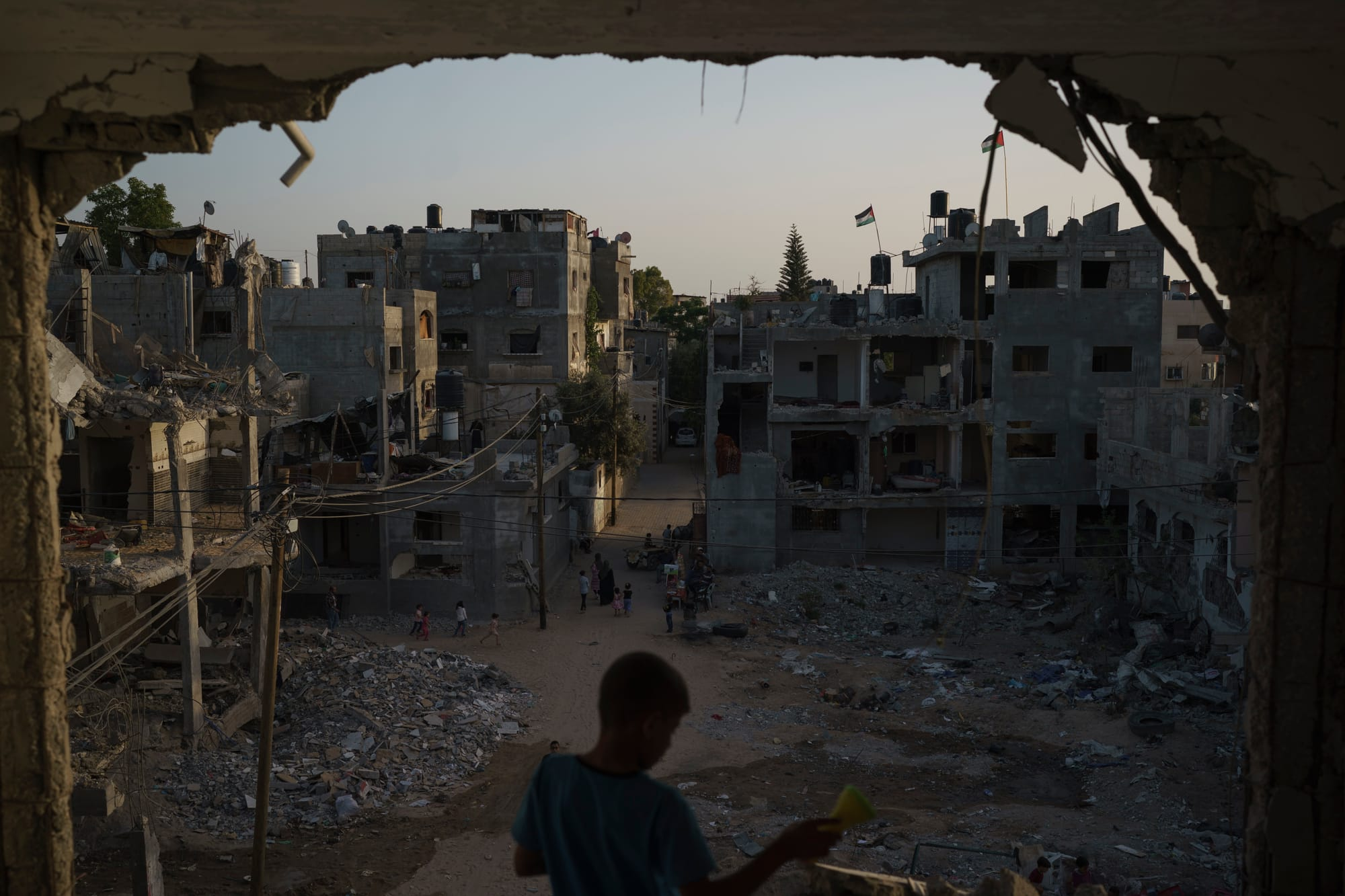 A young boy looks out from his home in Gaza that had been heavily damaged by airstrikes during a war between Gaza's Hamas rulers and Israel. The two have fought four wars over the last 13 years.