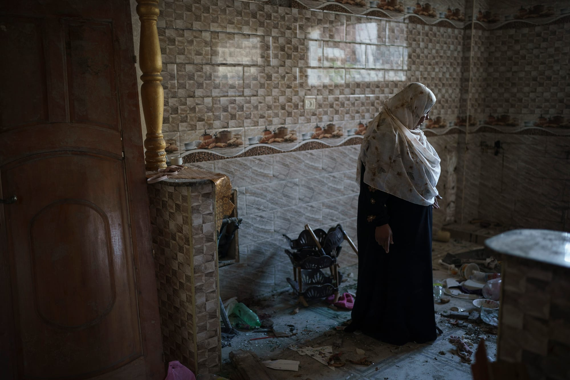 A woman, Khaldyia Nassir, stands in her house that had been heavily damaged by airstrikes in the recent 11-day war in Beit Hanoun.
