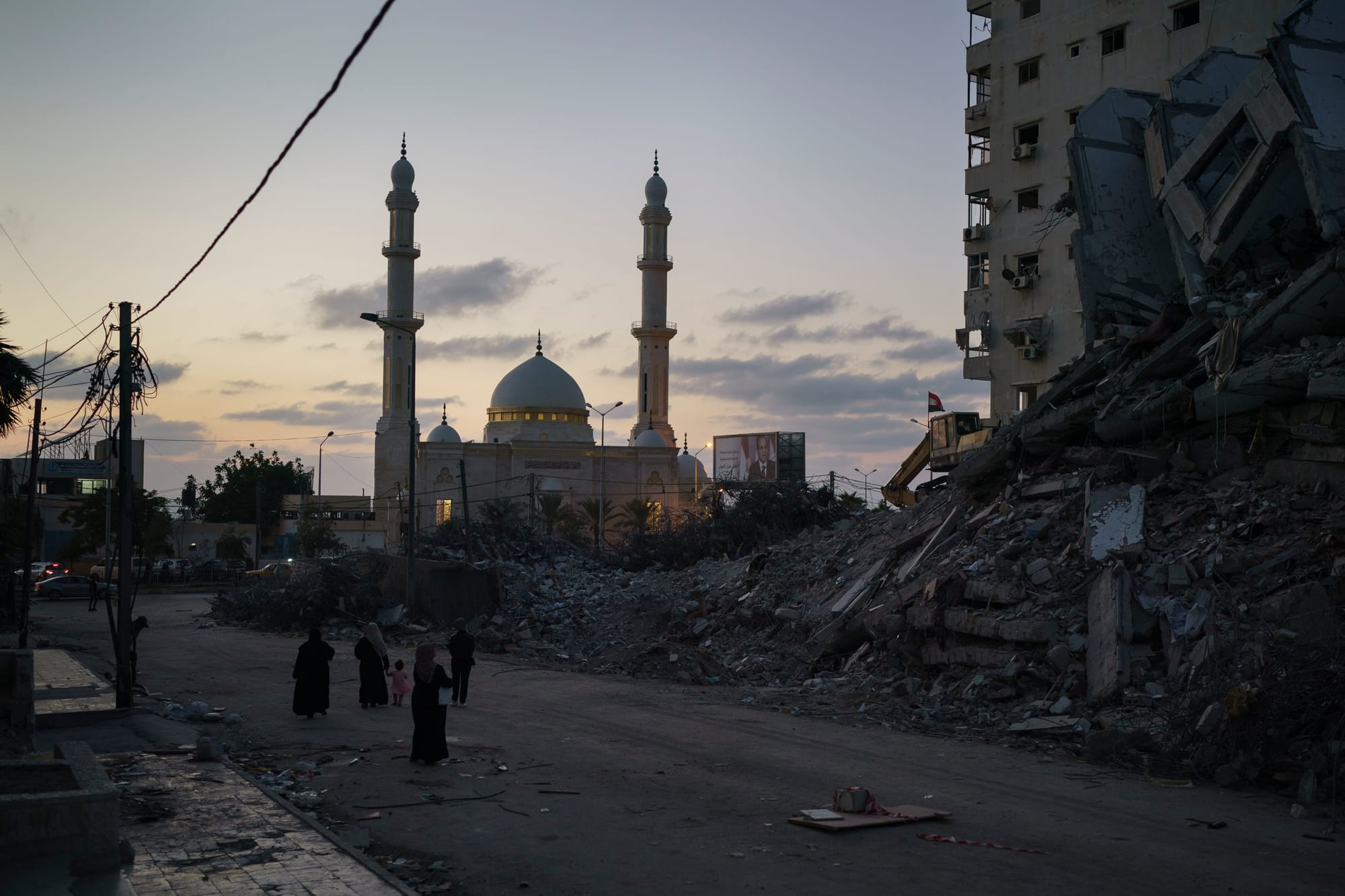 Palestinians walk next to the rubble of a destroyed building.