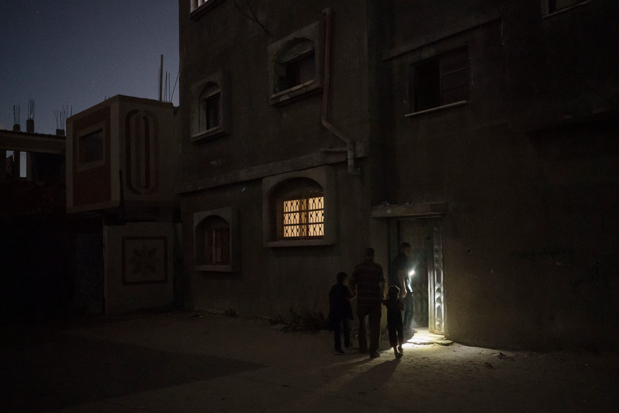 Zaki Nassir walks with his young sons at night to an apartment he rented after their house was damaged.