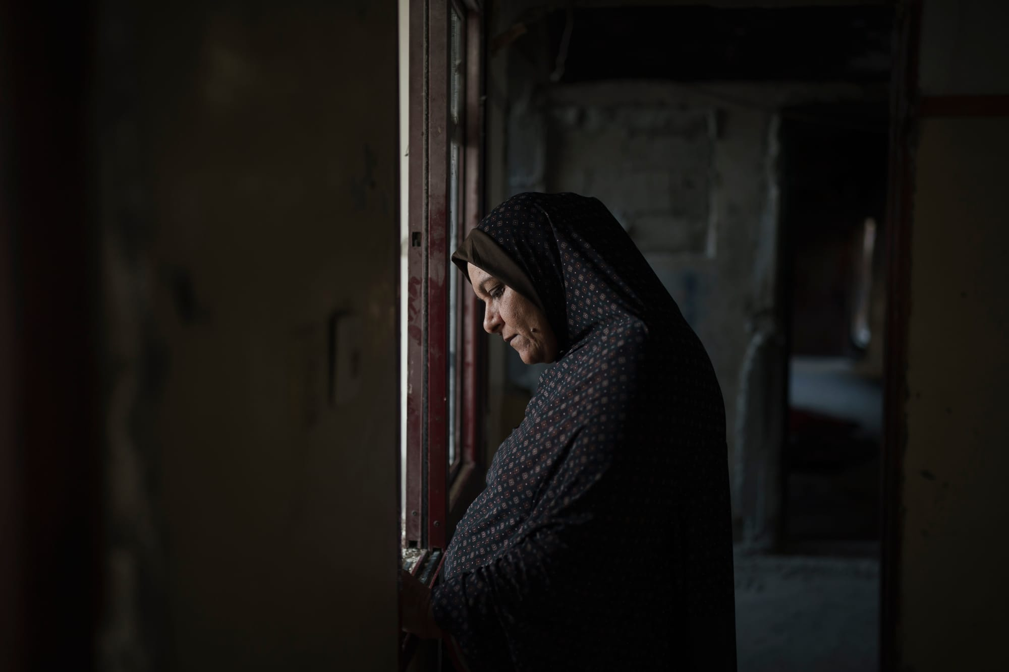 A woman, Jawaher Nassir, looks outside the window of her heavily-damaged home. The family lost a nephew in the first war and another in this year's war.