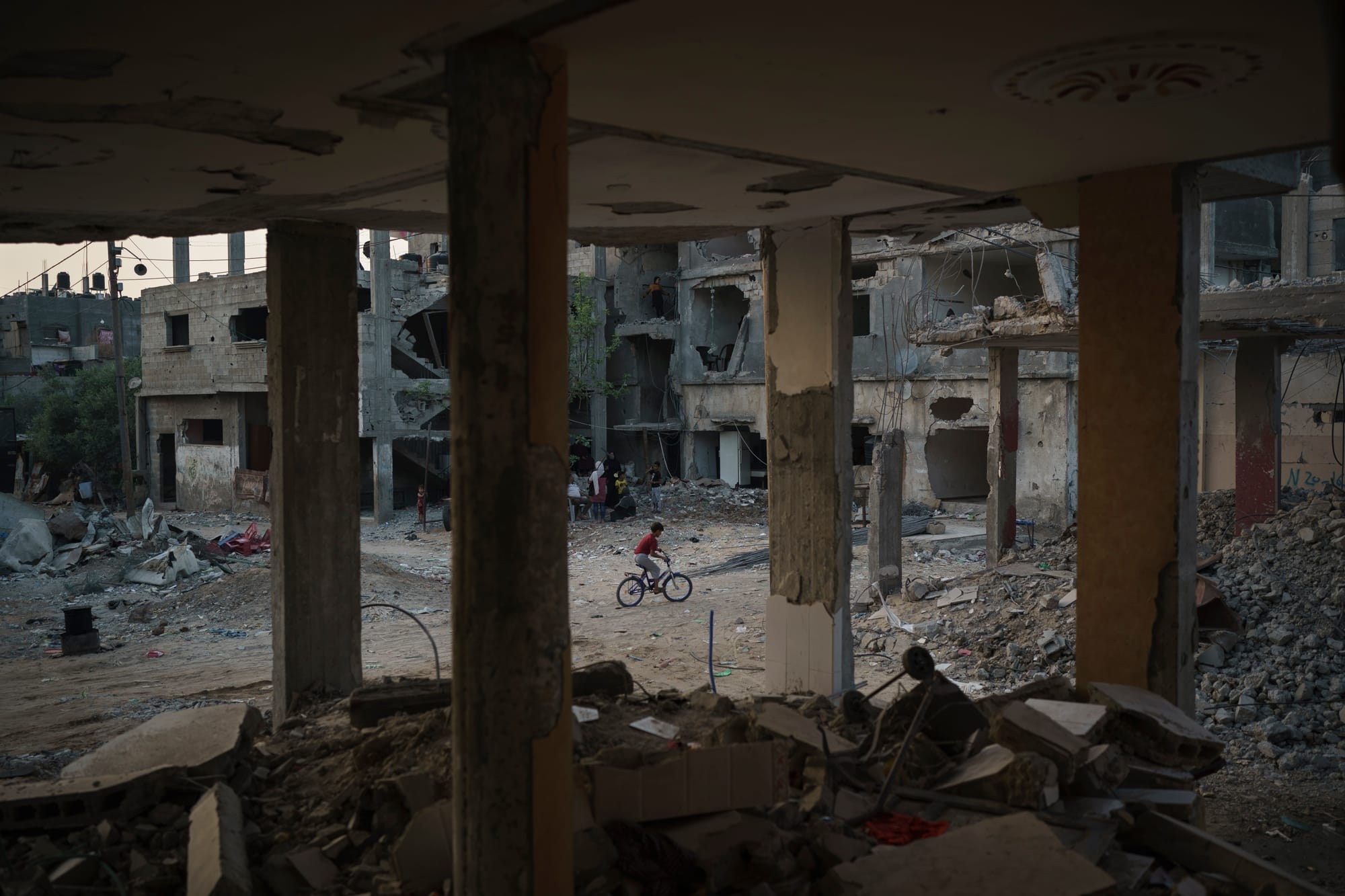 A boy rides his bike along a street next to houses heavily damaged by airstrikes during the recent 11-day war in Beit Hanoun in the northern Gaza Strip.
