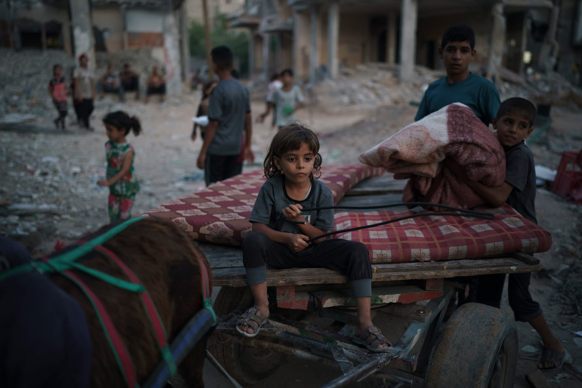 A 7-year-old boy sits on a donkey cart as his brother loads it with belongings from their damaged house.