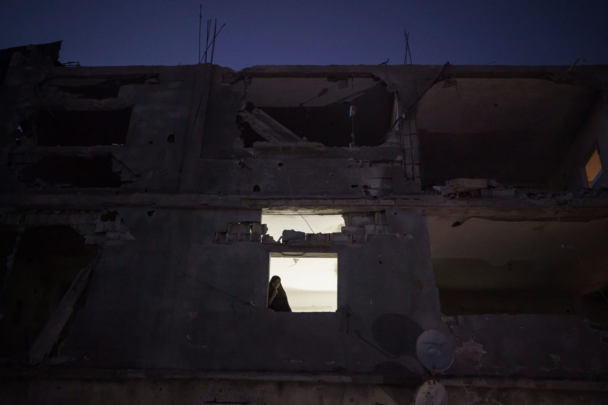 A window in the heavily damaged Nassir home is illuminated at night by a lamp, using electricity from a neighbor. The story of the Nassirs, their neighbors and the toll of four wars is Gaza's story.