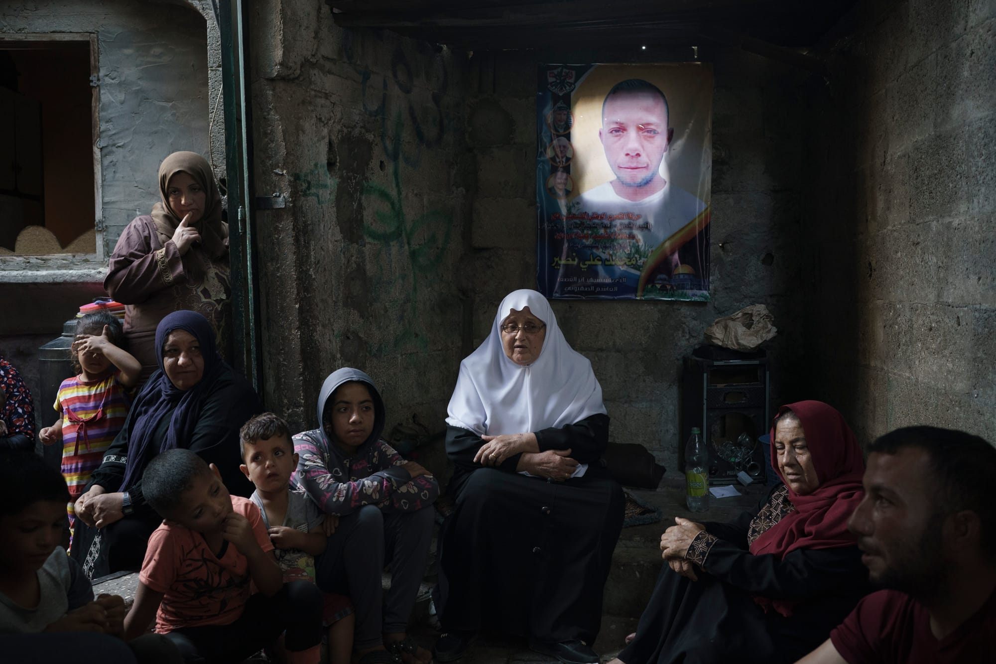 Around 10 members of a family sit on the floor of their home in Gaza. Above them is the poster of one of their relatives who died in a recent 11-day war between Gaza's Hamas rulers and Israel.