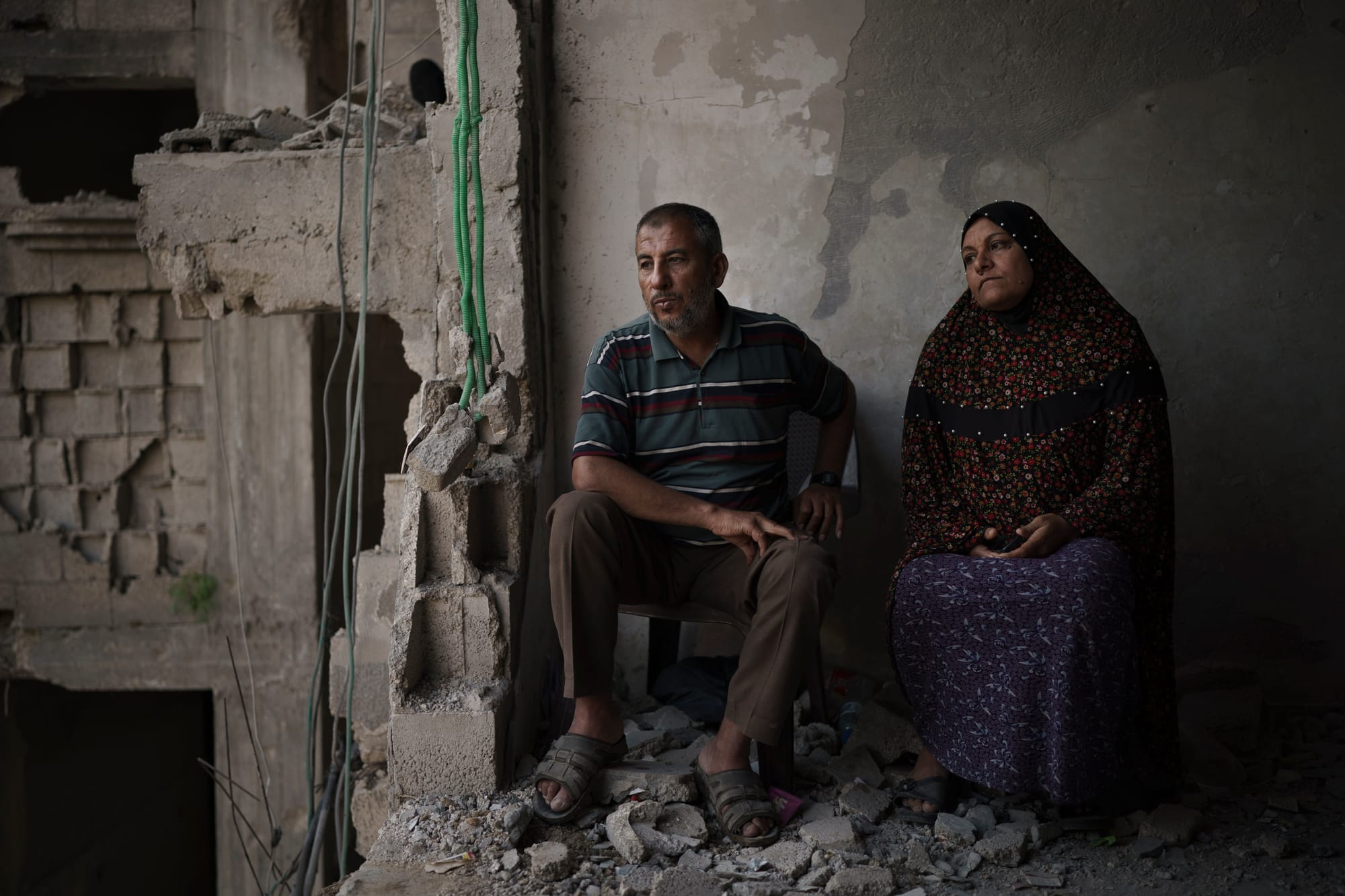 A man and a woman, Zaki and Jawaher Nassir, sit inside their home that had been heavily damaged by airstrikes in Beit Hanounon in the northern Gaza Strip.