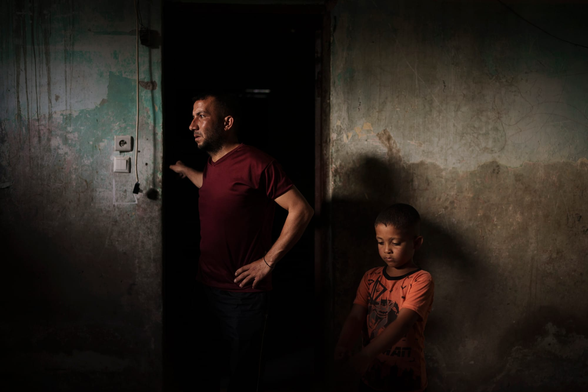 A man stands beside his young son in the doorway of their home in Gaza that had been damaged in an airstrike. Left behind are neighborhoods in shambles and families in mourning.
